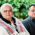 "Musqueam leaders, the late Delbert Guerin Sr., left, and the late Ernie Campbell, presided at the ""Victory Through Honour"" pole re-dedication ceremony at UBC, 2004. University of British Columbia Archives, Photo by Martin Dee (UBC 125.1/019)"